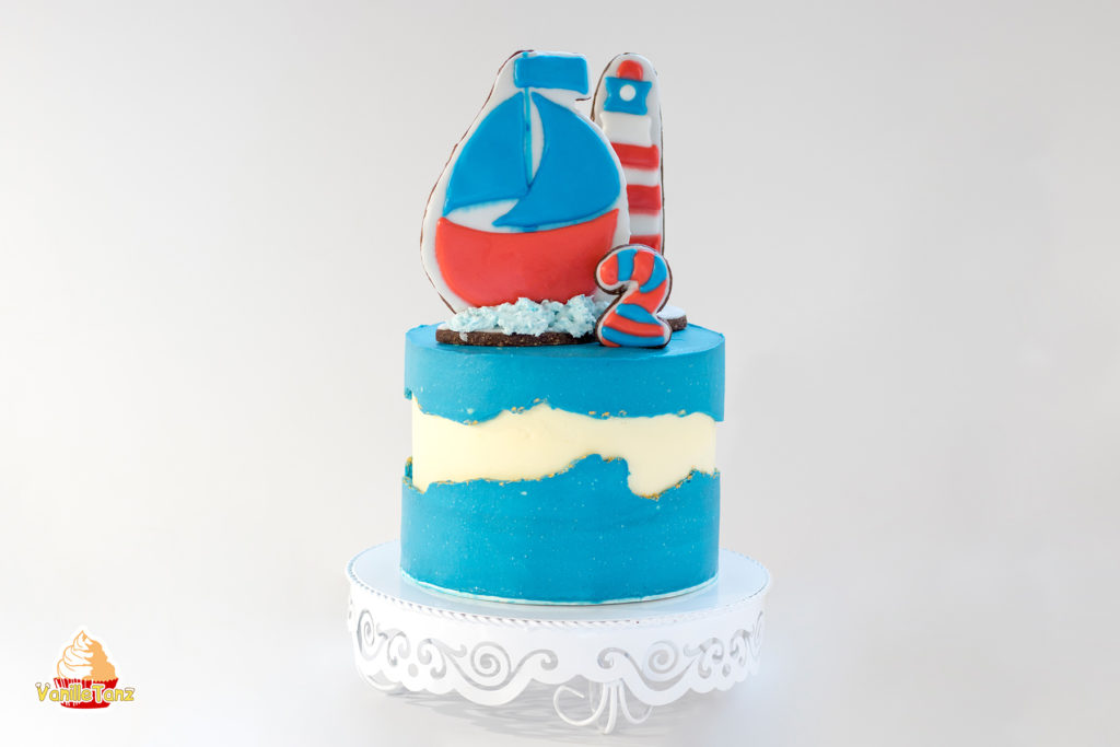 Torte für Kindergeburtstag. Dekoriert mit Keksen in Motiven Schiff, Ziffer 2 und Leuchtturm. Torte in Farbe blau.