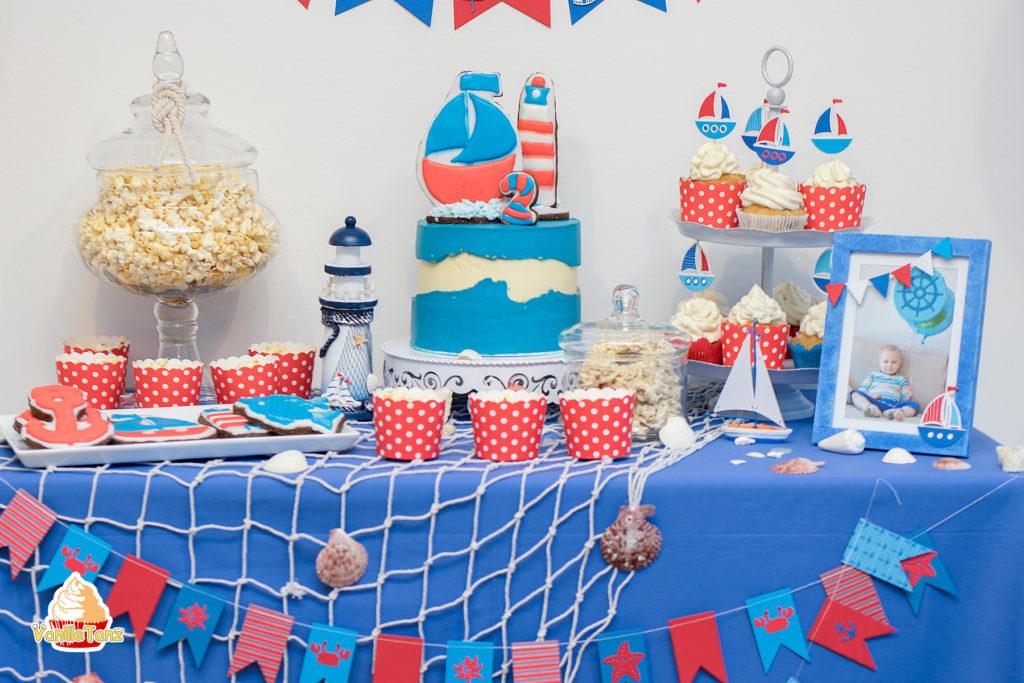 Candy Bar in Maritime Stil. Kindergeburtstag in Farben rot und blau. Popkorn, CuoCakes, Torte, Foto auf dem Tisch.
