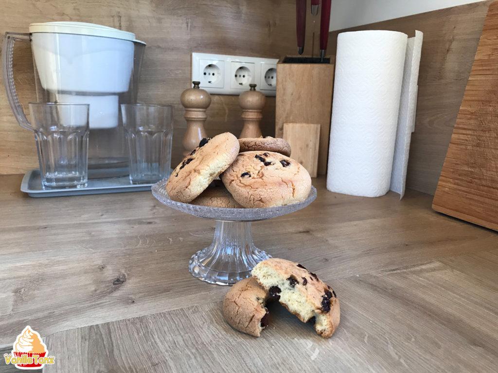 Kekse auf kleiner Glasetagere. Im Hintergrund stehen Wasserfilter, zwei Gläser, Salzmühle und Pfeffermühle, Messer und Küchenpapier Rolle
