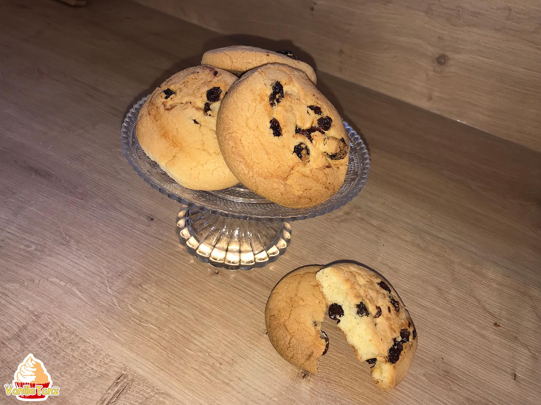Drei runde Kekse mit Rosinen auf einer Glasetagere. Daneben liegt ein geteilter runder Keks mit Rosinen.