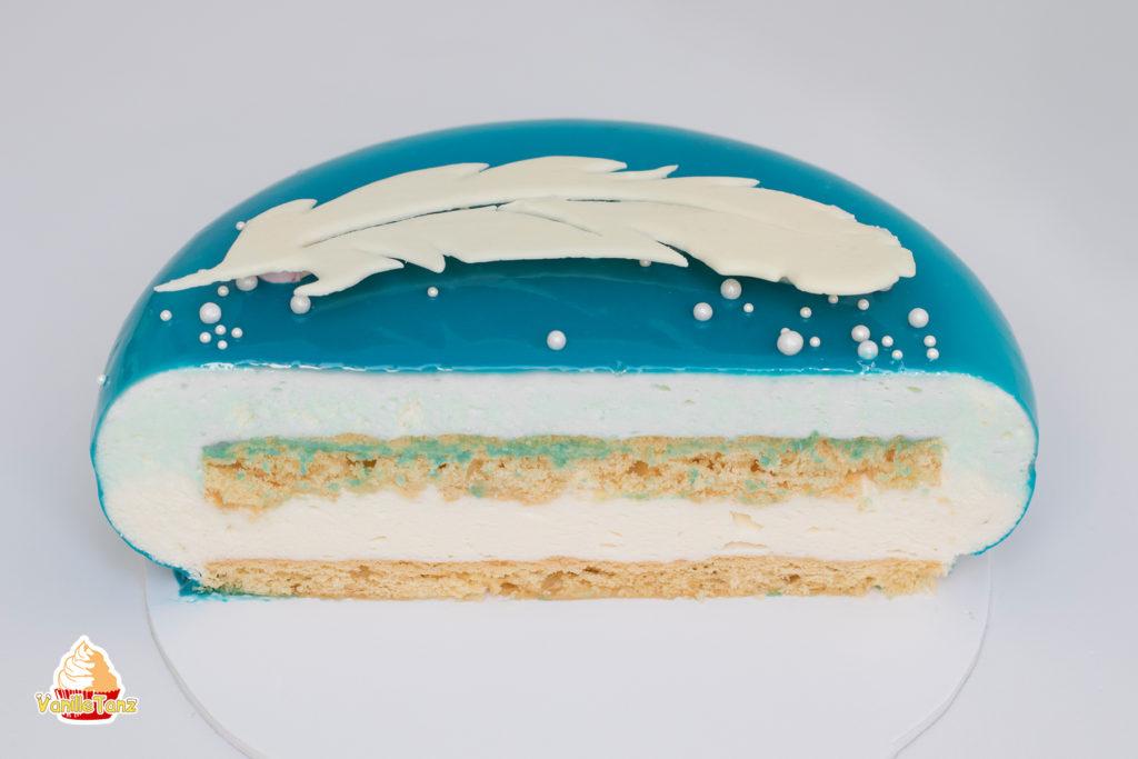 Anschnitt einer Torte. Vogelmilch Torte mit Feder aus weißer Schokolade. Moussetorte mit blauer Mirror Glaze.