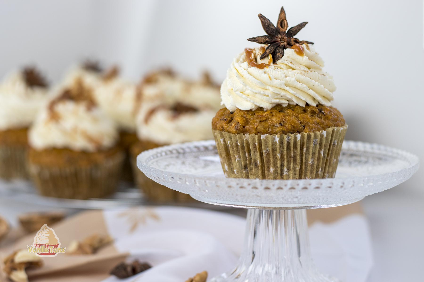 Karotten Cupcake mit Frischkäsecreme auf einem kleinem Tortenständer aus Glas. Braune Farbtöne