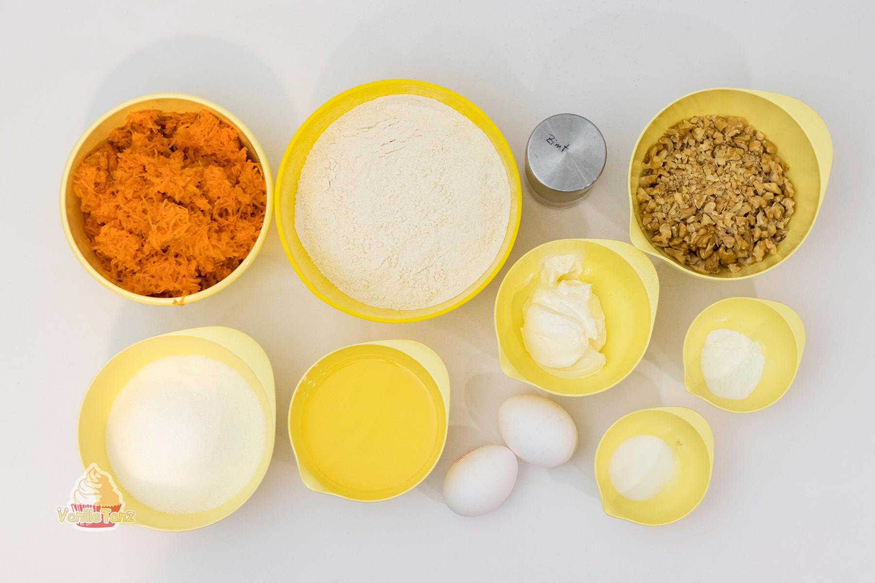 Schalen mit Zutaten für Karotten Muffin. geraspelte Karotten, Mehl, gehackte Nüsse, zwei Eier